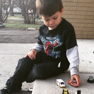 Kirby playing with matchbox cars